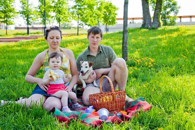 Rodzice, dziecko i pies piknik w parku.