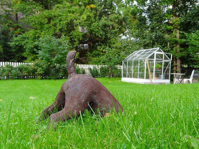 Figurka ogrodowa psa szukającego kości w trawie