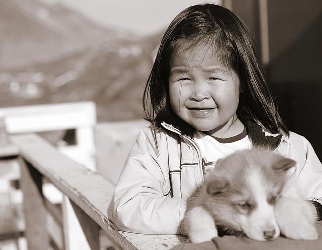 Dziewczynka Inuit trzymająca szczeniaka